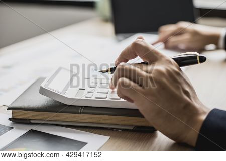 Close-up Man Holding A Pen And Pressing A Calculator, A Businessman Sitting In A Private Office At A