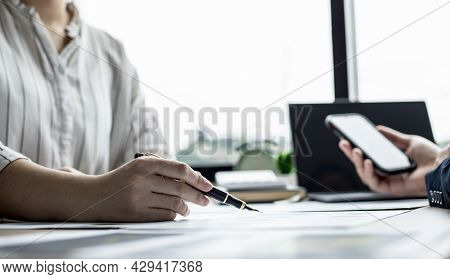 Two Businessmen Are Brainstorming Together And Reviewing The Company Financial Documents That The Fi