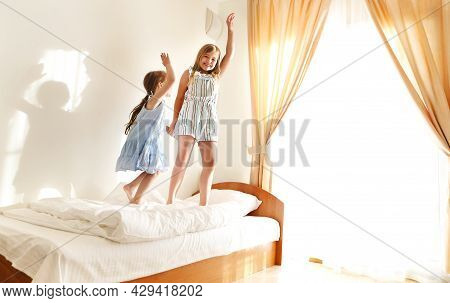 Two Cute Carefree Little Sisters Girls In Casual Clothes Playing Having Fun In Childrens Room In Sun