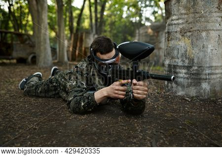 Paintball player shoots lying down on the ground