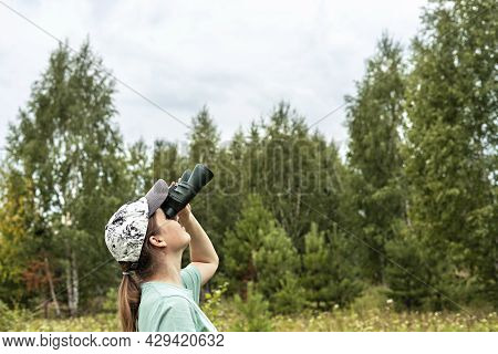Young Blonde Woman Bird Watcher In Cap And Blue Looking Through Binoculars At Cloudy Sky In Summer F