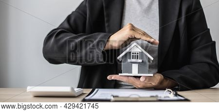 A Small Gray Model House Is An Example Of A Home In A Housing Project, An Insurance Salesperson Is D