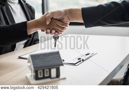 Salesperson And Customer Shake Hands After Signing The Contract, The Salesperson Explains The Detail