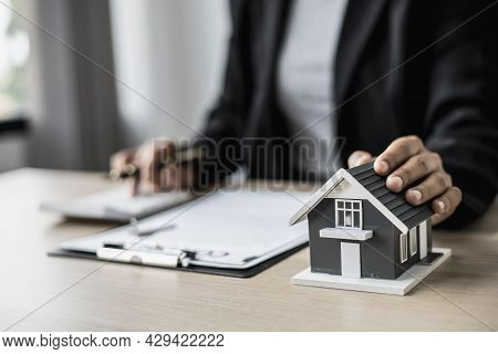 Small Gray House Model Is An Example Of A House In A Housing Project, The House Salesperson Checks T