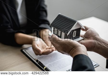 The Salesperson Handed The Small Gray Model Of The House And The House Keys To The Customer As A Sig