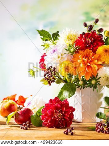 Autumn still life with garden flowers. Beautiful autumnal bouquet in vase, apples and berries on wooden table. Colorful dahlia and chrysanthemum.