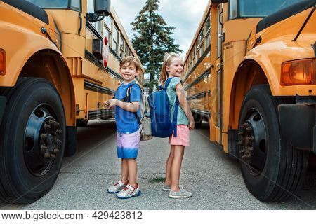 Happy Caucasian Children Boy And Girl Kids Students Standing By Yellow School Bus. Education And Bac