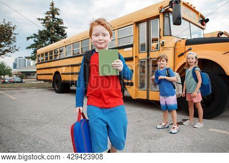 Happy Caucasian Children Boys And Girl Kids Students Standing By Yellow School Bus. Education And Ba