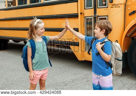 Children Boy And Girl Kids Students Give Hands High Five By Yellow School Bus. Education And Back To