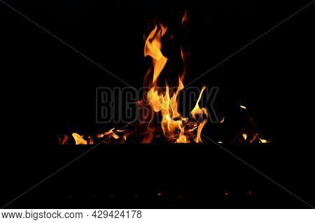Flames At Night. Fire Flames On Black Background.  Tongues Of Flame On The Background Of Coals
