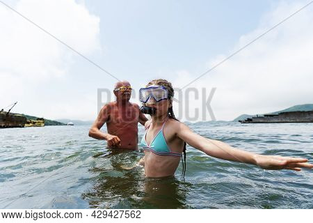 The Granddaughter And Grandfather With A Snorkel And A Mask Are Snorkeling Near The Sunken Ship.