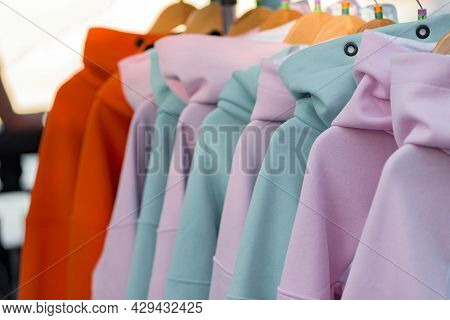 Closeup Photo Of Colorful Hoodies Hanging In Row For Sell, A Hoodie Is A Sweatshirt With A Hood