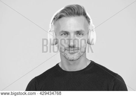 Charismatic Man Wearing Earphones. Concept Of Music And Digital Technology. Ebook And Elearning. Mat