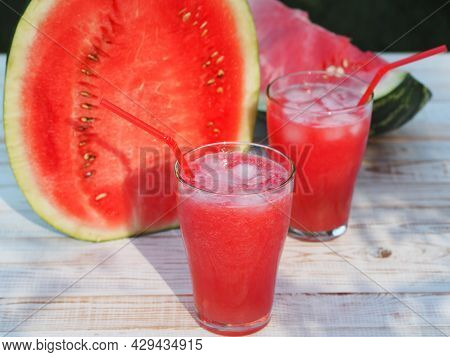 Glasses Of Cool Drink Made From Fresh Pulp Of Watermelon With Ice On A Wooden White Table With Slice