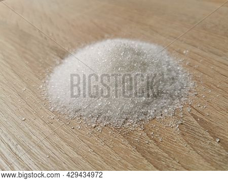 Pile Of Granulated White Sugar On Wooden Table