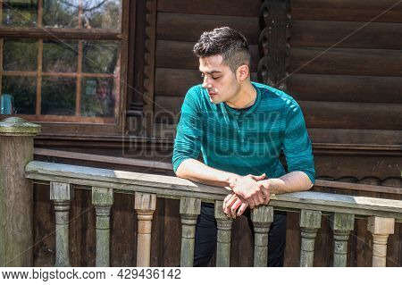 A Young Handsome Guy Is Standing By Wooden Railing And Into Deeply Thinking.