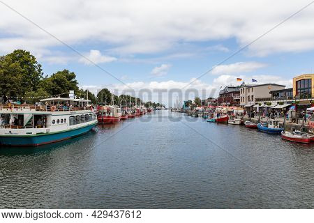 Rostock, Germany - July 20, 2021: Excursion boats and fishing boats at Alter Strom harbor of Warnemünde district at the Baltic Sea coast. Shopping mall on the right pier.