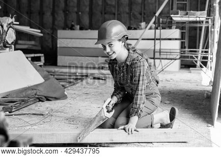Girl Working With Wood In Workshop. Carpentry And Woodwork Concept. Portrait Of A Cute Kid Posing As
