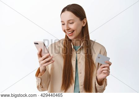 Online Shopping. Smiling Young Woman Make Order, Pay With Mobile Phone And Credit Card, Looking At S