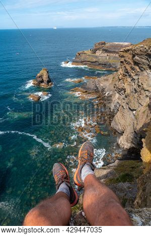 A Young Man Sitting On The Shoreline Looking At The Fort Des Capucins A Rocky, Clifftop Islet In The