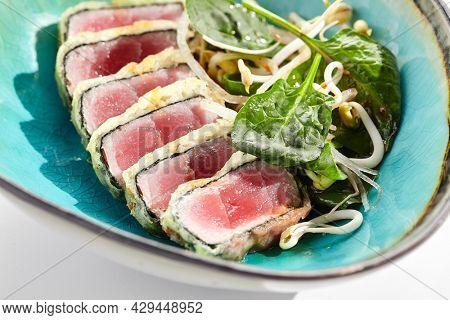 Tuna tataki - seared tuna,. thinly sliced sashimi style. Tuna tataki served with delicious citrus ponzu tataki sauce. Japanese seafood on black plate isolated on white background