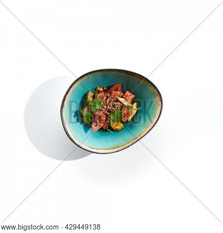 Salmon and avocado salad bowl. Blue salad bowl isolated on white background. Salad garnished with micro greens and sesame, chopped salmon, sliced avocado and parsley green leaf. Salmon with spicy sauc