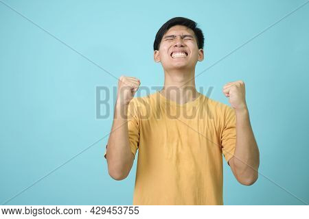 Young Man Over Blue Background Very Happy And Excited Doing Winner Gesture With Arms Raised, Smiling