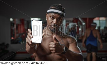 African American Guy Showing Phone With Blank Screen, Copy Space For Ad. Gym Workout And Sports App
