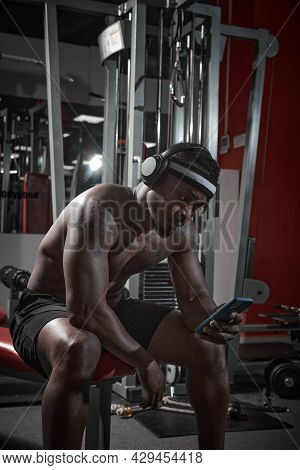 Athletic African American Man In Headphones With Phone Using Sport Apps Sitting On Sports Bench Duri