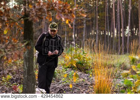 A Man In The Forest, A Hunter, A Mushroom Picker In A Military Cap Looks Down And Holds A Cigarette.