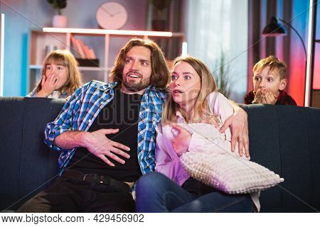 Little Girl And Boy Hiding Behind Couch While Their Parents Watching Thriller On Tv. Caucasian Famil