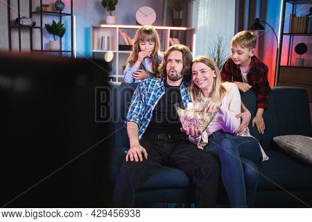 Happy Caucasian Family Of Four Eating Popcorn And Watching Television While Resting Together On Couc