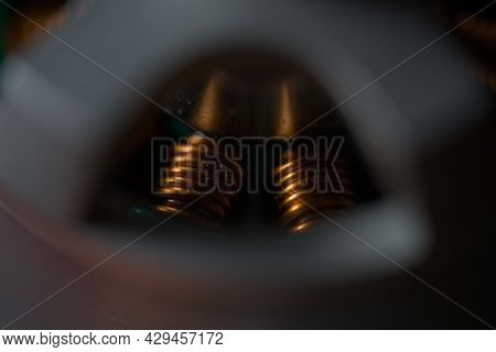 Dark Close Up Of Shiny Copper Coils Within A Brushless Drone Motor. Copy Space And Selective Focus W