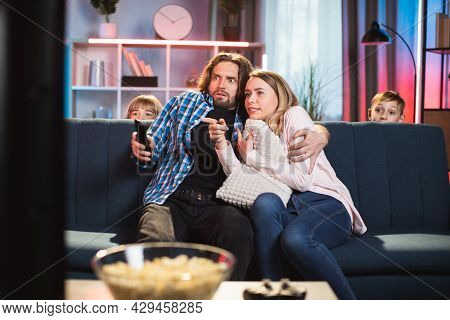 Scared Bearded Husband Hugging His Frightened Wife During, Watching Horror Film On Tv At Home In The