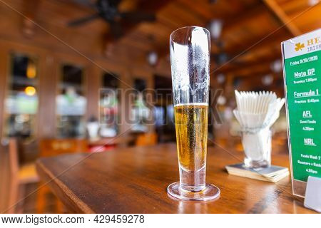 Kuala Lumpur, Malaysia - March 14, 2021: Beer On A Wooden Table In An Irish Pub. In The Background T