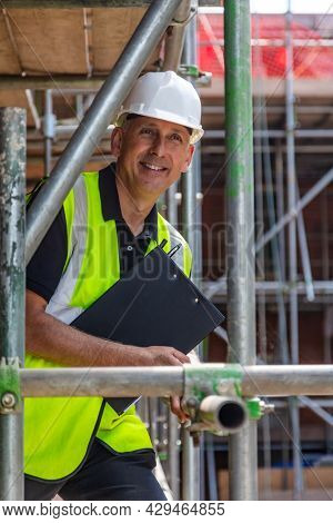 Male builder foreman, construction worker or site manager holding a clipboard, smiling, wearing a white hard hat and hi vis vest