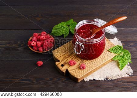 Raspberry Jam In A Glass Jar And Fresh Berries Bowl On A Dark Wooden Background. Conservation And Su