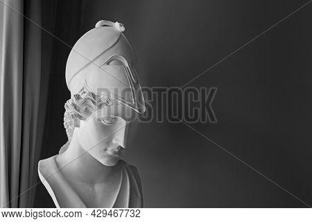 Ancient Greek goddess Athena Pallas statue on dark background with copyspace. Marble woman head in helmet sculpture