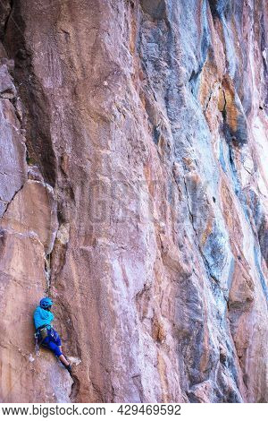 A Woman In A Helmet Climbs A Beautiful Blue Rock. Climbing Protective Equipment. Safety In Climbing.