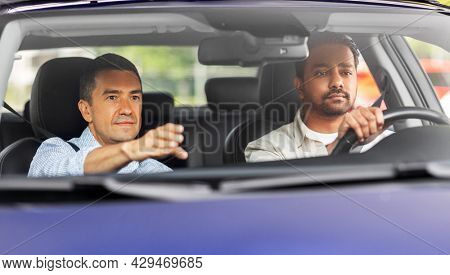 driver courses and people concept - car driving school instructor teaching young man to drive