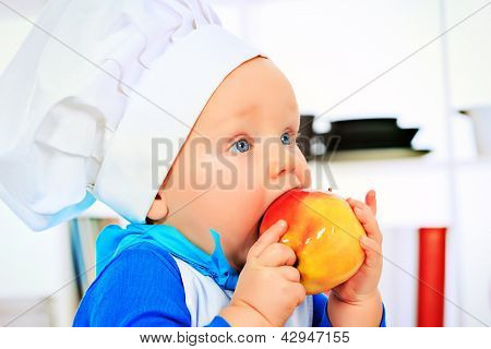 Cute small baby in the cook costume eating fresh apple at the kitchen.