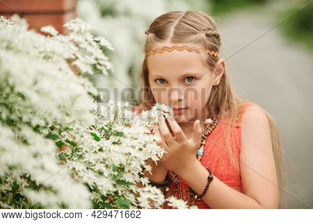Cute girl child dressed in hippie style stands next to flowering shrubs along the fence. Romantic hippie style.