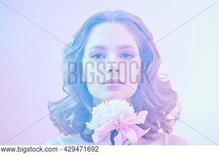 Portrait of a romantic beautiful young woman with gentle lilac-violet make-up holding a delicate peony flower. Beauty, perfumery and cosmetics.