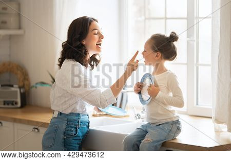 Happy day! Mom and her daughter child girl are playing, smiling in the kitchen. Family holiday and togetherness.