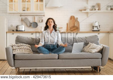 Happy young woman enjoying sunny morning and practicing meditation on the sofa at home.
