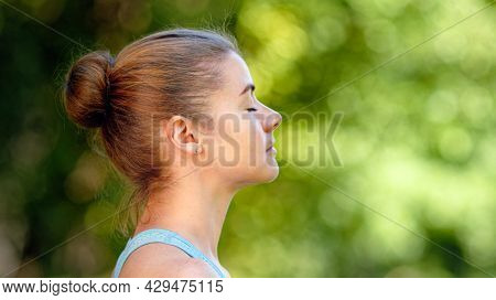 Young woman blonde sits in relaxing yoga pose on green park meadow grass