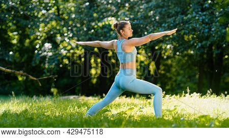 Young woman yoga trainer stands in static asana on green meadow grass