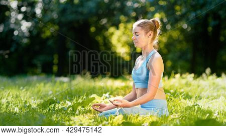 Lady athlete in blue tracksuit practices yoga sitting in relaxation pose