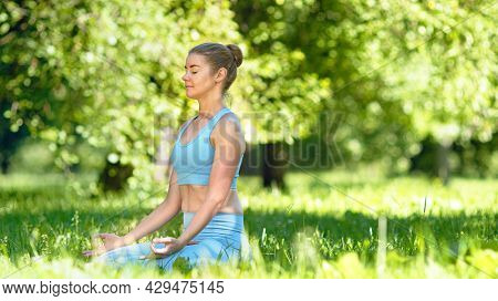 Concentrated blonde young woman in tracksuit practices breathing yoga exercises