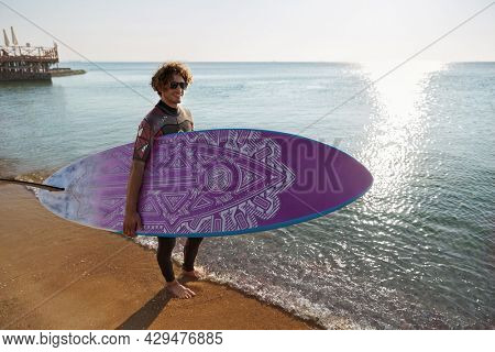 Young surfer holding surfboard on sandy beach coast with water waves. Smiling curly man wear diving suit and glasses. Concept of extreme water sport. Idea of summer vacation. Sunny daytime